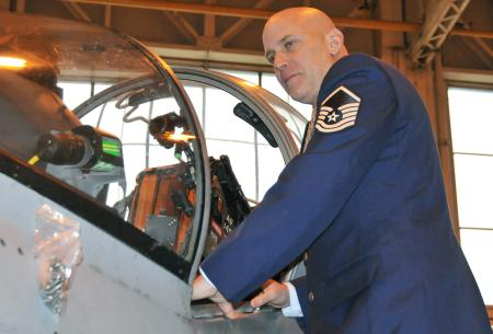 Master Sgt. Louis Distelsweig looks in the cockpit of a Harrier jet Jan. 11, 2011, at Royal Air Force Cottesmore, England. The aircraft was similar to ones his father, Capt. Louis Distelsweig Jr., flew during his time as an exchange pilot with the RAF in 1970.