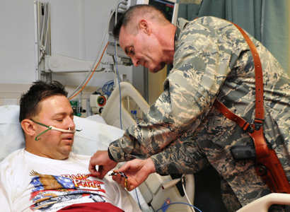 Brig. Gen. Darryl Roberson, the 455th Air Expeditionary Wing commander, pins a Purple Heart Medal on Tech. Sgt. James Davis, April 23, 2011, at the Craig Joint Theater Hospital. Sergeant Davis, a flight engineer with the 83rd Expeditionary Rescue Squadron, was shot in the leg during a mission to rescue the pilots of a downed Army helicopter. U.S. Air Force photo by Capt. Erick Saks