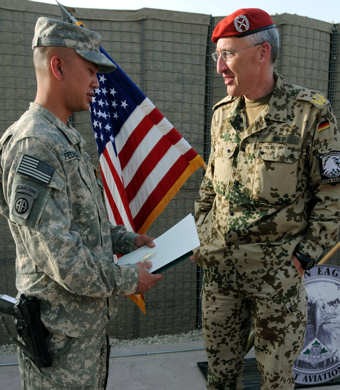 U.S. Army Maj. Robert Federigan, the 4th Combat Aviation Brigade medical operations officer, speaks with the Regional Command – North commander, German Maj. Gen. Markus Kneip, after receiving from him the Silver Bundeswehr (German military) Cross of Honor, April 25, 2011 for outstanding meritorious service in helping to orchestrate a mass casualty evacuation during an attack near Pol-e Khumri, Feb. 18, 2011.