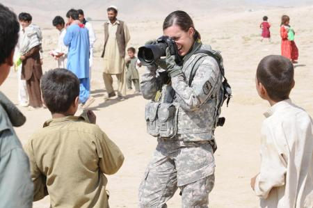 Military journalist Sgt. Rebecca Linder, of the 196th Maneuver Enhancement Brigade, South Dakota Army National Guard, takes photographs of Afghan children during a humanitarian mission Sept. 29, 2010, in Kabul, Afghanistan. Photo by Army Sgt. Matthew Nedved