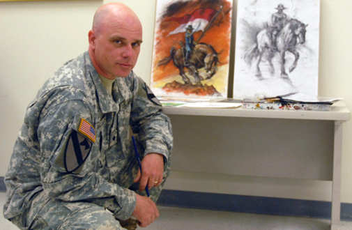 Spc. Scott Macaulay, from Boston, poses by his paintings, Feb. 25, 2011. Macaulay has been painting murals and signs throughout the brigade since his enlistment in 2009.