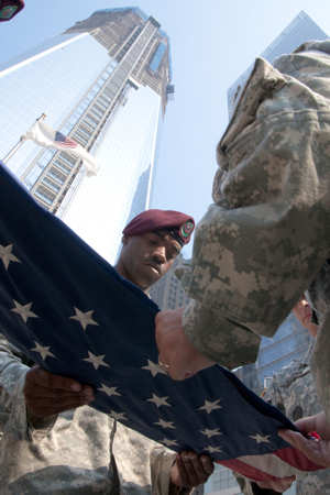 "Staff Sgt. Phillip McNair, a human resource specialist of the 404th Civil Affairs Battallion folds a U.S. flag just after it was raised here at ""Ground Zero"" the base of the World Trade Center. This flag has flown in over 30 different locations in Afghanistan and for the last time here at ""Ground Zero"" July 20, 2011. This flag was flown in every location for exactly 9 minutes and 11 seconds. This flag was flown originally here during the construction of the World Trade Center before being flown in Afghanistan. Photo by Army Sgt. 1st Class Andy Yoshimura"