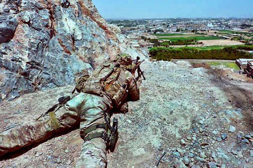 A U.S Army sniper watches through his weapon's scope and reports suspicious activities in Kandahar city, Afghanistan, July 25, 2011. The soldier is assigned to the 4th Infantry Division's Headquarters Company, 2nd Battalion, 8th Infantry Regiment, 2nd Brigade Combat Team. U.S. Army photo by Capt. Daniel Bustamante