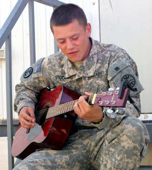 Pfc. Zac Stoddard, a driver with 1st platoon, Company F, 3rd Battalion, 116th Cavalry Regiment, 3rd Sustainment Brigade, 310th Sustainment Command (Expeditionary), strums a guitar during his free time at Joint Base Balad, Iraq on April 11, 2011.