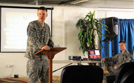 Capt. Dennis Jenson, at podium, chaplain with 1st Battalion, 18th Infantry Regiment, 2nd Advise and Assist Brigade, 1st Infantry Division, United States Division – Center and a Fergus Falls, Minn., native, reads from scripture at Sunday church service Feb. 6, 2011 at Camp Taji, Iraq.