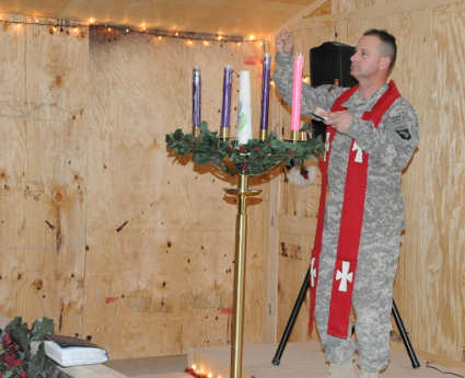 Army Chaplain (Maj.) Randal H. Robison lights the Advent candles during a Catholic Mass at the Frontline Chapel at Forward Operating Base Sharana, Afghanistan, December 24, 2010.