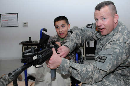 Erick Morales, 13, of Powell, Wyo., holds an M4 Carbine, with the help of Wyoming Army National Guard Lt. Col. Sam House, April 21, 2011, at the Camp Guernsey Joint Training Center Simulation Center, in Guernsey, Wyo. Erick spent the day at the Camp Guernsey Joint Training Center as an honorary soldier. Erick suffers from muscular dystrophy and scoliosis. The day was organized by the Wyoming National Guard after receiving a request from the Morales family to help Erick live his dream of becoming a soldier.