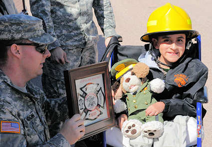 Erick Morales, 13, of Powell, Wyo., sports a Camp Guernsey Joint Training Center, in Guernsey, Wyo., fire helmet and a certificate presented to him by Staff Sgt. Alan Snook, the camp's fire chief, April 21, 2011.
