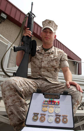 Sgt. Kenneth D. Nelson, training non-commissioned officer with the Assault Amphibious School Battalion, holds a rifle with his shooting badges displayed in front of him, June 9, 2011. Nelson recently shot at a competition earning him enough points to be a dual distinguished shooter.