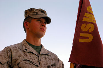 June 24, 2011 - Lance Cpl. Patrick Robertson, a reserve infantry Marine from Houston, stands in front of his unit's, 1st Battalion, 23rd Marine Regiment, flag, while serving in Afghanistan. Robertson is currently going to college to get his degree in mechanical engineering and then potentially become a commissioned officer in the Marine Corps.