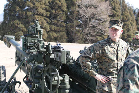 Sgt. Dustin Zimmerman, section chief, Gun Team 2, 3rd Battalion, 12th Marine Regiment, 3rd Marine Division, III Marine Expeditionary Force, prepares to explain the mechanics, characteristics, maintenance, firing protocol and new digital fire control system on the M777 Howitzer to Japan Ground Self Defense Force service members here Feb. 3, 2011. Photo by USMC Lance Cpl. Jovane Holland