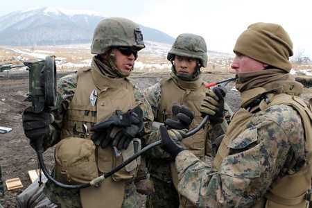 Marine Corps Cpl. Daniel Rivera, left, explains troubleshooting procedures to members of Gun Team 2 in support of the Artillery Relocation Training Program at the Hijudai Training Area, Japan, Feb. 8, 2011. Photo by USMC LCpl. Jovane M. Holland