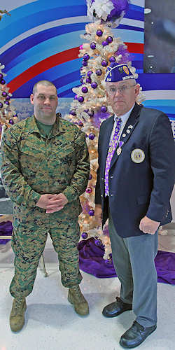 Staff Sgt. Daniel G. Stoy, an infantry unit leader with 8th Marine Regiment, 2nd Marine Division and Verl H. Matthews, the commander of the Military Order of the Purple Heart Beirut Memorial Chapter 642, stand in front of the Purple Heart Memorial Trees at the Marine Corps Base Camp Lejeune, N.C., Post Exchange on Dec. 7, 2011. The trees have 530 ornaments with the names of service members who have been killed in action. Photo by USMC Cpl. Andrew D. Johnston