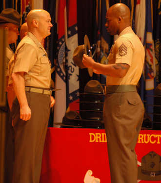Staff Sgt. Michael Riggs Jr. receives his campaign cover from Col. Robert Gates during the Drill Instructor School graduation ceremony for Class 2-11, March 23, 2011. Riggs was voted the best leader in the class by his peers, for which he was also awarded a trophy.