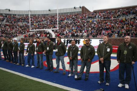 Marines representing part of Wounded Warrior Battalion-East from Marine Corps Base Camp Lejeune and Brooke Army Medical Center aboard Fort Sam Houston, Texas, stand in the end zone of the Armed Forces Bowl 2010 post-season college football game to be recognized by the thousands of fans in the Gerald J. Ford Stadium in Dallas, Dec. 30, 2010. The trip to Dallas was a two-part event, where not only were the wounded warriors able to attend a football game and be recognized, but also distribute resumes to various big-name corporations for job opportunities after they leave the service.