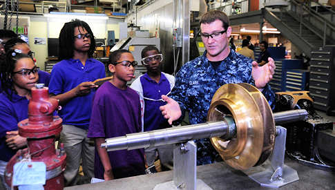 April 27, 2011 -- Machinist's Mate 2nd Class Chad Clark, assigned to the aircraft carrier USS Theodore Roosevelt (CVN 71), working at the Northrop Grumman's Light Industrial Facility, demonstrates how pump and valve equipment are repaired to students from Campostella Elementary School in Norfolk, Va. Students are touring the facility to correlate Campostella's science, technology, engineering and mathematics program to the industrial work Sailors do on a daily basis. Theodore Roosevelt is undergoing refueling complex overhaul at Newport News Shipbuilding.