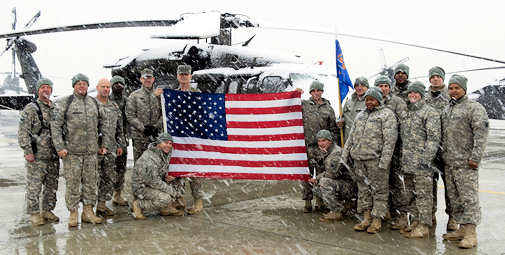 Members of A Company, 1-69 Aviation Regiment, hold the flag from Ground Zero, as snow falls at Bagram Air Base, Afghanistan, March 2, 2011. The 1-69 fly Blackhawk helicopters on various missions, from escorting VIPs to transporting detainees. Photo by British Sgt. Chris Hargreaves