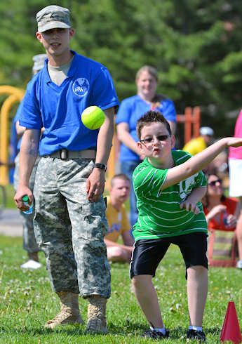 Mitchell Lehman, 8, a student at South Jefferson shows off his pitching techniques to his 'buddy', Pvt. Franklin Nelson, an infantryman assigned to Alpha Company, 2nd Battalion, 22nd Infantry Regiment, 1st Brigade Combat Team, 10th Mountain Division (LI) May 18, 2012 at the Monti Physical Fitness Center Athletic Fields during Special Olympics Day on Fort Drum. The event brought special needs students and soldiers together for a local community outreach program. Photo by Army Staff Sgt. Jennifer Bunn