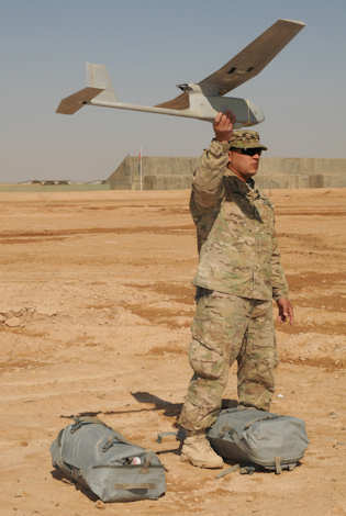 Army Sgt. Matthew Hair from the 594th Transportation Company, holds the RQ-11 Raven in the air during function checks of the system on Feb. 22, 2012. The Raven is used to video record the possible burying of IEDs and insurgent activity. Hair participated in a class to give soldiers more experience with the system. Photo by Army Sgt. Laura Bonano