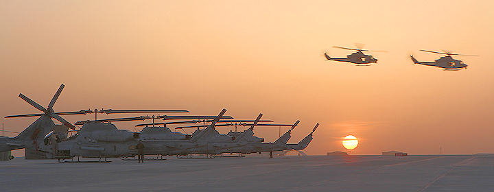 "The sun sets as UH-1Y Huey crews with Marine Light Attack Helicopter Squadron 369, the ""Gunfighters,"" fly across the flight line on Camp Bastion, Afghanistan, April 1, 2012. The Gunfighters continued combat operations while celebrating their 40th anniversary. Photo by USMC Cpl. Lisa Tourtelot"