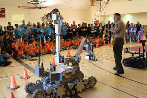 Sgt. Ryan Manke, an explosive ordnance disposal technician with Headquarters and Headquarters Squadron and a McMinnville, Ore., native, speaks about the Mk 3 Mod. 0, a robot used to disable or relocate explosives during a robotics tournament at Bernardo Heights High School in San Diego, March 20, 2012. The Marines, based out of Marine Corps Air Station Miramar, Calif., presented three machines to students ranging from kindergarten to high schoolers taking part in the robotics program. Photo by USMC Pfc. Christopher Johns