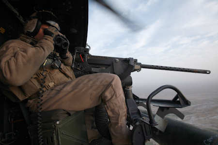 Sgt. Jason Sparks, a native of Savannah, Ga., and a door gunner for Marine Light Attack Helicopter Squadron 369, scans for suspicious activity while providing air support for Marines from 1st Light Armored Reconnaissance Battalion in Helmand province, Afghanistan on March 15, 2012. Helicopters from the squadron often provide aerial security for Marines participating in ground operations. Photo by USMC Cpl. Isaac Lamberth