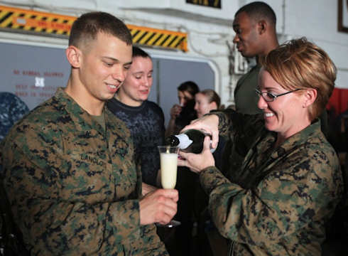 Marine Gunnery Sgt. Jennifer E. Holt, right, pours cider Jan. 1, 2012 aboard USS Makin Island for Marine Lance Cpl. Ryan A. Langlois in celebration of the new year. Holt, who hails from Tampa, Fla., serves as imagery chief for the 11th Marine Expeditionary Unit. The unit left San Diego Nov. 14, 2011 for a regularly scheduled deployment to the Western Pacific and Middle East regions. Langlois, 20, an electrical engineer, hails from New Bedford, Mass. Photo by USMC Lance Cpl. Claudia M. Palacios
