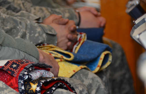 Soldiers, who recently returned from deployment, sit with their quilts during a Quilts of Valor ceremony at the Bamberg Chapel in Germany, Feb. 29, 2012. During the ceremony, 33 Soldiers were presented with quilts donated by The Beachlovin' Grannies of the Carolinas. The Quilts of Valor foundation has donated more than 61,000 quilts to combat service members and veterans throughout the world. Photo by Sina Kingsbury, USAREUR