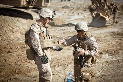 Petty Officer 3rd Class Michael Soto, right, gives medical supplies to Lance Cpl. Nathan A. Morningstar during the construction of a bridge in Garmsir, Helmand province, Afghanistan, Jan. 30, 2012. Courtesy photo
