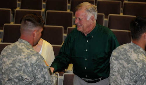 "Jimmy Gentry, a World War II veteran, shakes hands with soldiers of the 101st Sustainment Brigade following his story at the ""Holocaust Day of Remembrance"" at Wilson Theater, April 16, 2012. Gentry spoke to the soldiers about the impact that April 29, 1945, had on his life; that day his unit in World War II liberated the Dachau concentration camps and its 32,000 surviving detainees. Photo by Army Spc. Michael Vanpool"