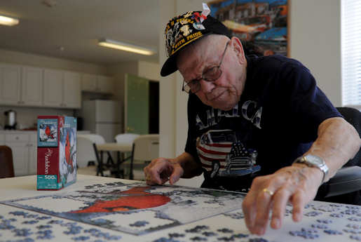 John Coons, a former U.S. Army private first class and World War II veteran, puts together a jigsaw puzzle at the community center near his Hampton, Va. home, June 6, 2012. The puzzles offer Coons a mental reprieve from the post-traumatic stress disorder symptoms he still experiences from his time as a soldier. Photo by USAF Senior Airman Jarad Denton