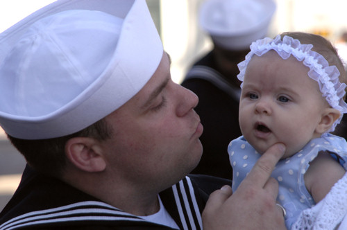 U.S. Navy Petty Officer 3rd Class Rick Pfeifer embraces his 3-month old daughter for the first time at the homecoming ceremony for guided missile cruiser USS Bunker Hill in San Diego, March 13, 2007.