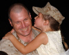 Lt. Col. Andrew Kennedy, 3rd Battalion, 4th Marine Regiment battalion commander, gets a welcome home kiss from his daughter Katherine on July 31. Around 800 Marines and Sailors returned from Iraq over the weekend. � is the first ground unit to complete three rotations in Iraq. Photo by: Cpl. Heidi E. Loredo
