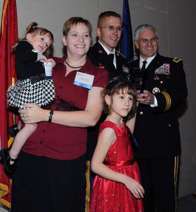 Tawny Campbell of Landstuhl, Germany holds Rhynli, 2, as Ceilidha, 7, looks out at the sea of photographers. Sgt. Joe Campbell stands with Army Chief of Staff Gen. George Casey Jr. who presented their award on behalf of the National Military Family.