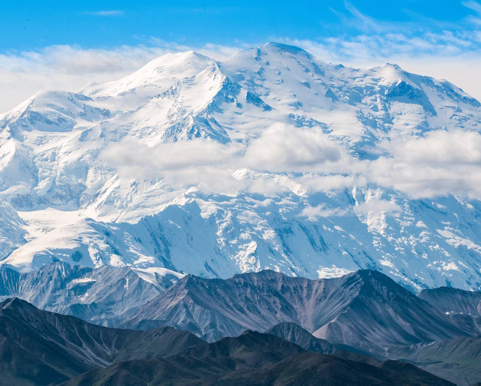 A stunning, awe inspiring view of Denali, North America's tallest mountain at 20,310 feet, towering above smaller mountains haloed by clouds under the blue sky of Alaska. (Image created by USA Patriotism! from U.S. National Park Service photo.)