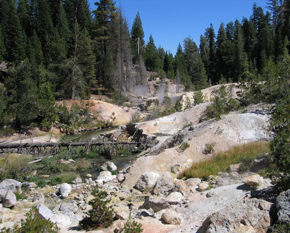 A steaming view of the Devils Kitchen hydrothermal area with Hot Springs Creek flowing through it at Lassen Volcanic National Park. Devil's Kitchen is full of fumaroles and mudpots. (Image created by USA Patriotism! from U.S. National Park Service.)