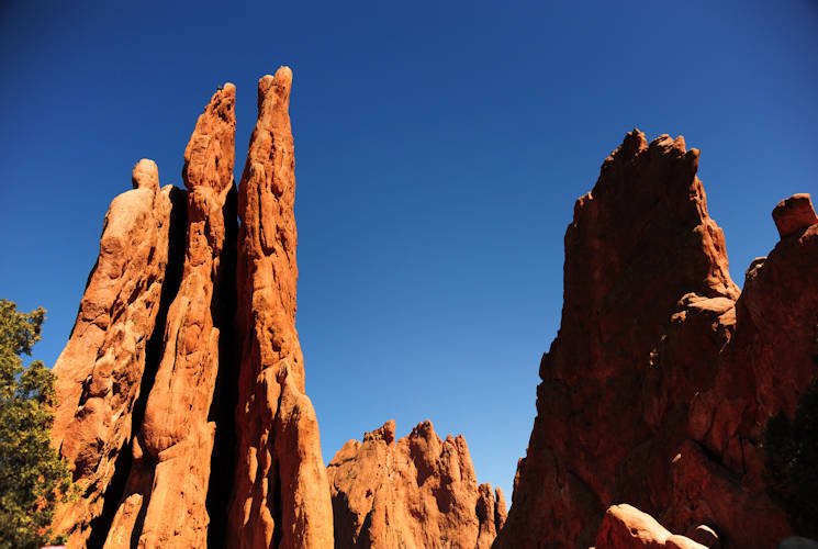 April 7, 2016 - The Three Graces, a triple spire sandstone formation, glows red-orange in the noonday sun at the Garden of the God . The Three Graces is just one of the many famous rock formations visible as you travel the 15 miles of trails throughout the park. (U.S. Air Force photo by Staff Sgt. Amber Grimm)