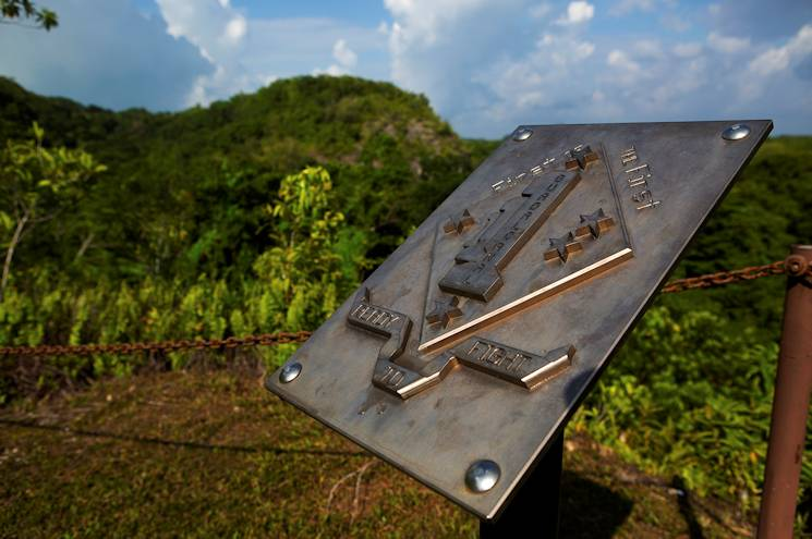 A plaque dedicated to the 1st Marine Division sits atop Bloody Nose Ridge at the 1st Marine Division Memorial on the Island of Peleliu, Palau, Sept. 15, 2014. This year marks the 70th Anniversary of the landing on Peleliu, in which Marines from the 1st Marine Division fought in and was one of the bloodiest battles during World War II in the Pacific. (U.S. Marine Corps photo by Cpl. Erik Estrada)