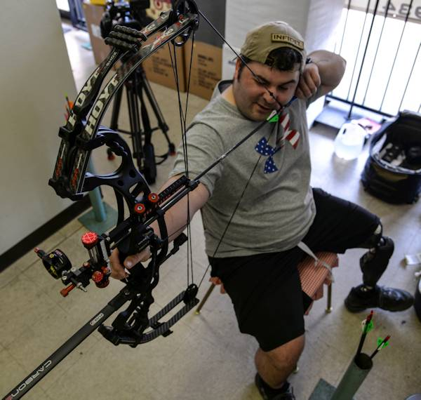 U.S. Air Force Staff Sgt. Seth Pena, former tactical control air party member and now member of the 59th Medical Wing Patient Squadron, aims his compound bow at his target at a local archery shop in San Antonio, Sept. 12, 2014. After being injured by a drunk driver who ran a red light, Pena practices archery for hours each to week to keep busy. (U.S. Air Force photo by Senior Airman Michael Ellis)