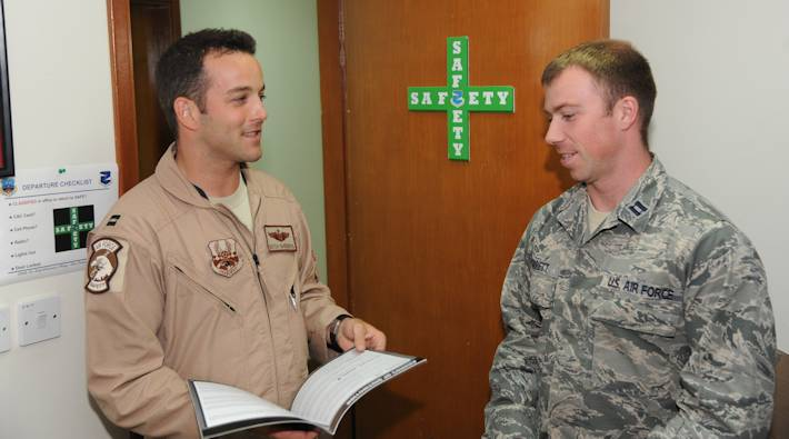 U.S. Air Force Capt. Brett VanderPas, left, 380th Air Expeditionary Wing chief of flight safety, speaks with U.S. Air Force Capt. Zach Garrett, 380th Expeditionary Medical Group aerospace physiologist, in the safety office at an undisclosed location in Southwest Asia, July 10, 2013. The safety office and the aerospace physiologist work closely together to monitor trends preventable by changing human factors. (U.S. Air Force photo by Senior Airman Jacob Morgan)