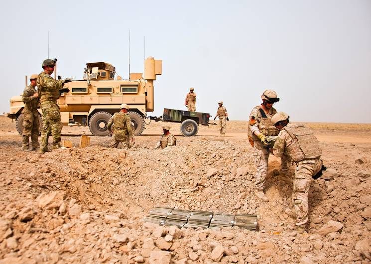 U.S. Air Force and Slovakian explosive ordnance disposal personnel unload a trailer and carefully place ordnance for a controlled detonation June 12, 2013, near Kandahar Airfield, Afghanistan. U.S. Air Force, U.S. Army, Slovakian and Australian EOD personnel participated in a joint mission to dispose of excess military ordnance. (U.S. Air Force photo by Senior Airman Scott Saldukas)