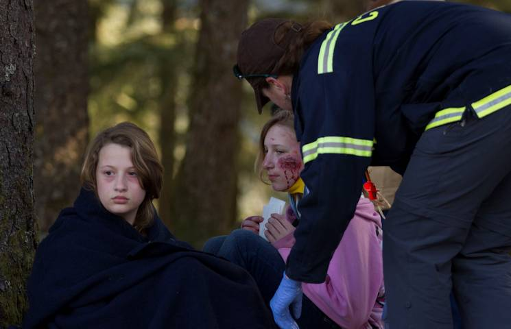 An EMT with the Cordova Volunteer Fire Department provides care to members of Girl Scout Troop 285 after they were pulled from the debris of a simulated roof collapse at The Red Dragon as part of a mock disaster drill in conjunction with Alaska Shield 14 here, March 28, 2014. Alaska Shield 14 is an exercise that involves state, federal, military and local agencies, designed to test the response and coordination of the disaster modeled after the 1964 earthquake and subsequent tsunami that devastated much of South Central Alaska including the city of Cordova. (U.S. Army photo by Sgt. Shane Dorschner)