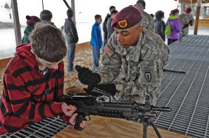 U.S. Army Pfc. Anthony Golden with Charlie Company, 3rd Battalion, 509th Infantry, 4th Brigade Combat Team (Airborne), 25th Infantry Division, instructs a student from Gruening Middle School how to safely and properly handle the M249 squad automatic weapon at Joint Base Elmendorf-Richardson May 16, 2013. (U.S. Army photo by Sgt. Eric-James Estrada)