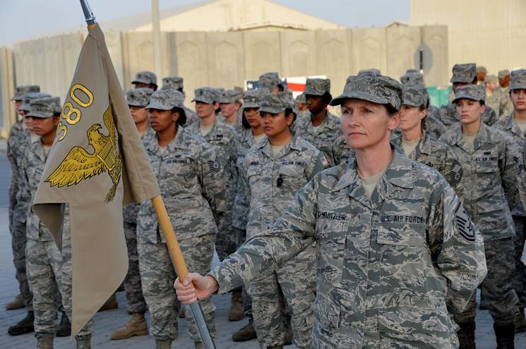Master Sgt. Linda Schwartzlow holds the guidon in formation with the 380th Air Expeditionary Wing at Al Dhafra Air Base, United Arab Emirates, March 8, 2013. Schwartzlow is the Air National Guard 2014 Outstanding First Sergeant of the Year. (U.S. Air Force photo by Staff Sgt. Timothy Boyer)