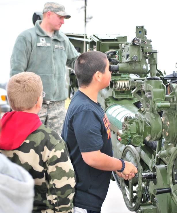 Students from Gatesville Intermediate School look at a M777A2 howitzer while Spc. Matthew Allen with Alpha Battery, Fires Squadron, 3rd Cavarly Regiment, stands by to answer questions during the school's career day in Gatesville, Texas on December 13, 2013. (Photo by Capt. Soutira Graham, 120th Infantry Brigade, Division West Public Affairs)