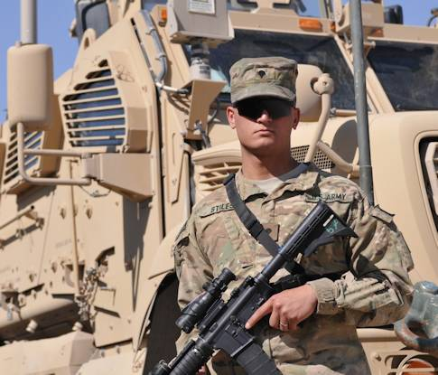 Spc. Nikolaus Stiles, a tank driver assigned to Company C, 1st Battalion, 64th Armor Regiment, 2nd Brigade Combat Team, Third Infantry Division and Lethbridge, Alberta, Canada native, stands by his Mine Resistant Ambush Protected All-Terrain Vehicle, Oct. 20, 2012, in Kandahar Airfield, Afghanistan. After participating in a naturalization ceremony on Nov. 2, 2012, Stiles plans to change his military occupational specialty and make a 20-year career of the Army. Photos by Army Sgt. Uriah Walker