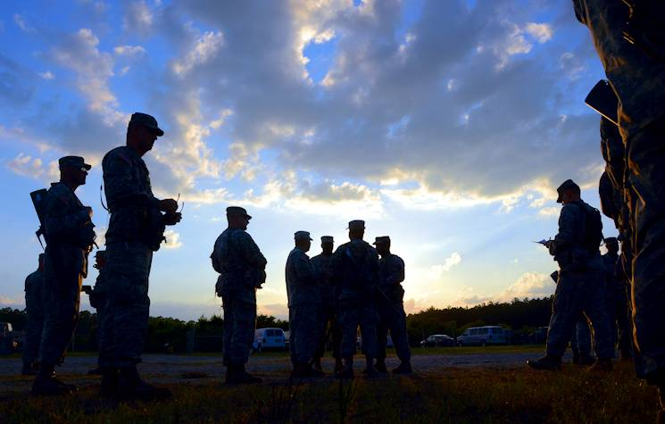 The sun sets on another Georgia sky as truck drivers with the 298th Transportation Company huddle together with members of the 327th Quartermaster Battalion for their evening safety brief and update, during the Quartermaster Liquid Logistics Exercise (QLLEX), June 10, 2014. The 2014 QLLEX is being used this year to provide a testing platform for two new capabilities being considered for the liquid logistics community. (U.S. Army photo by Sgt. William A. Parsons)