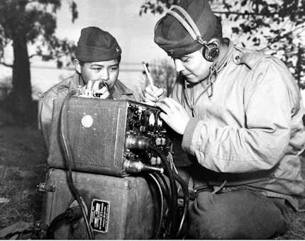 Pfcs. Preston Toledo and Frank Toledo, both Navajo Code Talkers and cousins, relay orders in the Navajo language on a field radio. They were attached to a Marine artillery regiment in the South Pacific. This photo was taken July 7, 1943. Courtesy Photo