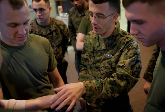 Petty Officer 2nd Class Michael Pappas, a hospital corpsman at Marine Barracks Washington, D.C., explains to Company A Marines how to properly apply a bandage on a wound during a Combat Lifesaver Course at the Barracks, Jan. 31, 2013. (Official Marine Corps photo by Pfc. Dan Hosack)