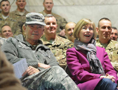 Army Gen. Martin E. Dempsey, chairman of the Joint Chiefs of Staff, and his wife, Deanie, enjoy a USO show with service members at Bagram Airfield, Afghanistan, Dec. 16, 2011. Through social media and contacts with service members and families, Deanie Dempsey discusses issues that include programs for military families overseas, jobs for military spouses, military family health, and her travels with the chairman. USAF photo by Airman 1st Class Cody Ramirez
